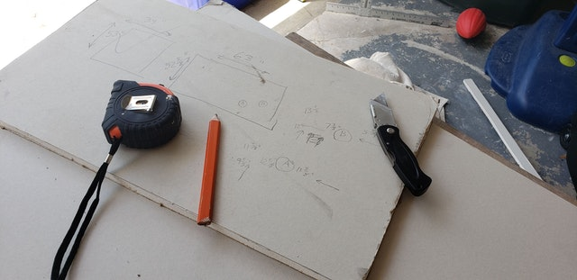 utility knife, measuring tape and a pencil on top of plasterboard