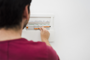 a man turning off the electrical fuse box